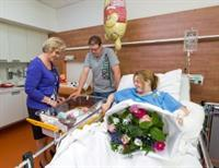 Betty van de Walle – voorzitter RvB Elkerliek ziekenhuis– overhandigt een feestelijk boeket en een welkomstpakket aan Samantha Beekers en Joris Goijaerts Zij zijn –  met baby Milan – de allereerste gasten in de nieuwe gezinssuite